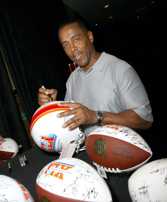 Former Dallas Cowboys running back Tony Dorsett signing footballs.