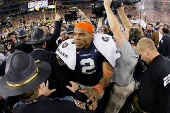 Auburn quarterback Cam Newton is swarmed by officers following the Tigers' 2010 National Championship win over Oregon