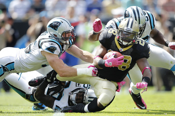 Panthers linebackers Dan Connor (55) and James Anderson (50) converge upon Saints running back Mark Ingram (28).