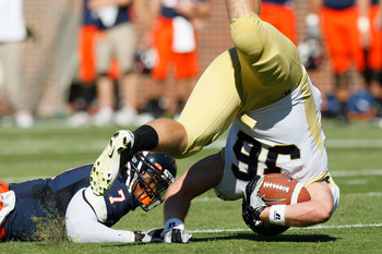 ATLANTA - OCTOBER 09:  Lucas Cox #36 of the Georgia Tech Yellow Jackets is upended by Corey Mosley #7 of the Virginia Cavaliers at Bobby Dodd Stadium on October 9, 2010 in Atlanta, Georgia.  (Photo by Kevin C. Cox/Getty Images)