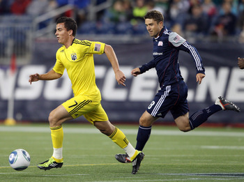 Columbus's Bernardo Anor, left, dribbles past New England's Chris Tierney.