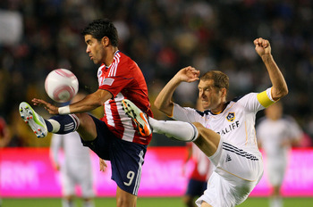 LA Galaxy captain Gregg Berhalter with the challenge on Chivas USA's Juan Pablo Angel.