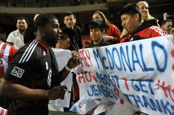 D.C.'s Brandon McDonald signs autographs for fans following the match.