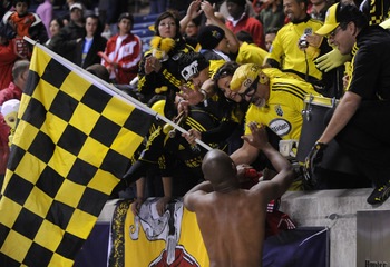 One of the Columbus Crew players exchanges high fives with the Nordecke, who traveled to Toyota Park on Saturday. The Crew lost to the Chicago Fire, 3-2.