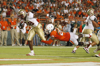 MIAMI, FL - OCTOBER 9: Jermaine Thomas #38 of the Florida State Seminoles breaks the tackle of Ray-Ray Armstrong #26 of the Miami Hurricanes to score a touchdown in the second quarter on October 9, 2010 at Sun Life Stadium in Miami, Florida. (Photo by Joe