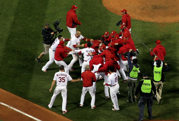The St. Louis Cardinals mob David Freese at home following his tenth inning walk off.