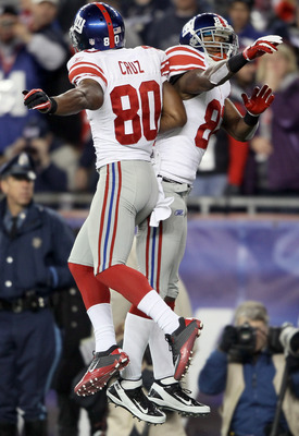FOXBORO, MA - NOVEMBER 06:  Mario Manningham #82 of the New York Giants is congratulated by teammate  Victor Cruz #80 after Manningham scored a touchdown in the fourth quarter against the New England Patriots on November 6, 2011 at Gillette Stadium in Fox