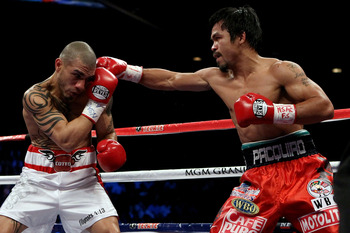 LAS VEGAS - NOVEMBER 14:  (R-L) Manny Pacquiao throws a right to the head of Miguel Cotto during their WBO welterweight title fight at the MGM Grand Garden Arena on November 14, 2009 in Las Vegas, Nevada.  (Photo by Al Bello/Getty Images)