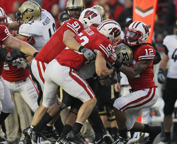 MADISON, WI - NOVEMBER 05: Raheem Mostert #8 of the Purdue Boilermakers is gang-tackled by Dezmen Southward #12, Mike Taylor #53 and Jordan Kohout #91 of the Wisconsin Badgers at Camp Randall Stadium on November 5, 2011 in Madison Wisconsin. Wisconsin def
