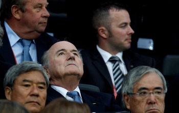 Sepp Blatter checks the branding on the corporate zeppelin whilst others watch the game.