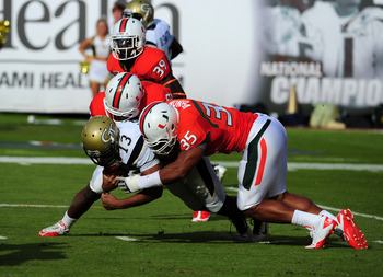 MIAMI GARDENS, FL - OCTOBER 22: Tevin Washington #13 of the Georgia Tech Yellow Jackets is tackled by Olivier Vernon #35 and Andrew Smith #48 of the Miami Hurricanes at Sun Life Stadium on October 22, 2011 in Miami Gardens, Florida. (Photo by Scott Cunnin