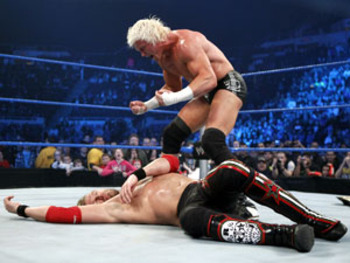 Dolph Ziggler attacks a beaten Edge.