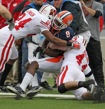 CHAMPAIGN, IL - NOVEMBER 19: A.J. Jenkins #8 of the Illinois Fighting Illini is hit by Shelton Johnson #24 and Chris Borland #44 of the Wisconsin Badgers at Memorial Stadium on November 19, 2011 in Champaign, Illinois. Wisconsin defeated Illinois 28-17. (