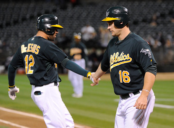 OAKLAND, CA - SEPTEMBER 15: David DeJesus #12 of the Oakland Athletics celebrates with Josh Willingham #16 after hitting a three-run home run against the Detroit Tigers in the first inning of an MLB baseball game at O.co Coliseum on September 15, 2011 in