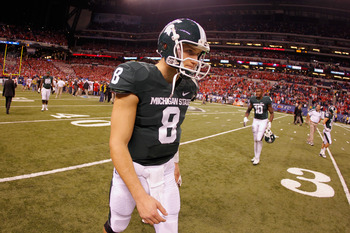 Spartans QB Kirk Cousins walks off the field after losing the Big Ten Championship Game to Wisconsin, 42-39.