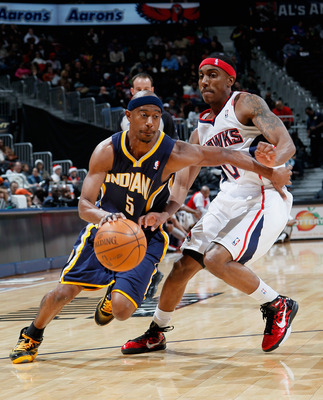ATLANTA, GA - DECEMBER 11:  T.J. Ford #5 of the Indiana Pacers drives past Jeff Teague #0 of the Atlanta Hawks at Philips Arena on December 11, 2010 in Atlanta, Georgia.  NOTE TO USER: User expressly acknowledges and agrees that, by downloading and/or usi
