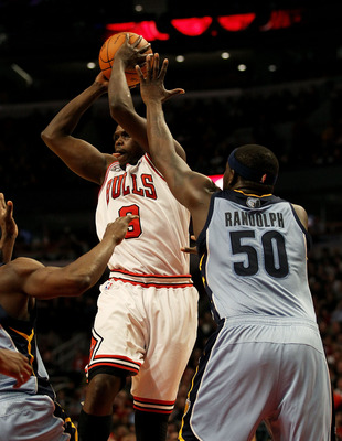 CHICAGO, IL - MARCH 25: Loul Deng #9 of the Chicago Bulls leaps to pass over Zach Randolph #50 of the Memphis Grizzlies at the United Center on March 25, 2011 in Chicago, Illinois. The Bulls defeated the Grizzlies 99-96. NOTE TO USER: User expressly ackno