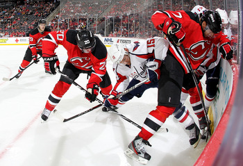 NEWARK, NJ - NOVEMBER 11: Ryan Carter #20 and Henrik Tallinder #7 of the New Jersey Devils and Jeff Halpern #15 and Brooks Laich #21 of the Washington Capitals battle for the puck at Prudential Center on November 11, 2011 in Newark, New Jersey.  (Photo by