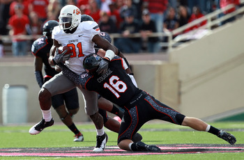 LUBBOCK, TX - NOVEMBER 12:  Justin Blackmon #81 of the Oklahoma State Cowboys is tackled by Zach Winbush #27 and Cody Davis #16 of the Texas Tech Red Raiders at Jones AT&T Stadium on November 12, 2011 in Lubbock, Texas.  (Photo by Ronald Martinez/Getty Im
