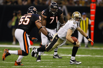 NEW ORLEANS, LA - SEPTEMBER 18:  Drew Brees #9 of the New Orleans Saints runs under pressure from  Israel Idonije #71 of the Chicago Bears at Louisiana Superdome on September 18, 2011 in New Orleans, Louisiana.  The Saints defeated the Bears 30-13.  (Phot