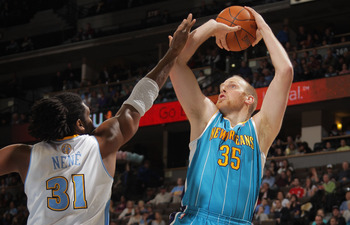 Chris Kaman splashes a shot in Nene's face.