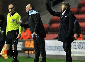 Roberto Mancini waves an invisible red card from the touchline