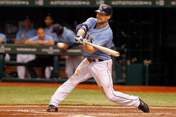 ST PETERSBURG, FL - OCTOBER 04:  Casey Kotchman #11 of the Tampa Bay Rays hits a RBI single in the fourth inning score Sean Rodriguez #1 against the Texas Rangers in Game Four of the American League Division Series at Tropicana Field on October 4, 2011 in