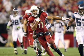 GLENDALE, AZ - JANUARY 01:  Wide receiver Larry Fitzgerald #11 of the Arizona Cardinals runs with the football after a reception against the Seattle Seahawks during overtime of the NFL game at the University of Phoenix Stadium on January 1, 2012 in Glenda