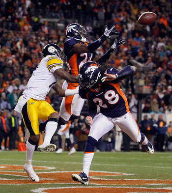 DENVER, CO - JANUARY 08:  Champ Bailey #24 of the Denver Broncos nearly intercepts a pass intended for Mike Wallace (L) #17 of the Pittsburgh Steelers, as Quinton Carter #28 of the Denver Broncos looks on during the AFC Wild Card Playoff game at Sports Au