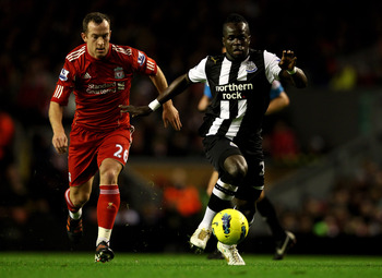 LIVERPOOL, ENGLAND - DECEMBER 30:  Cheik Tiote of Newcastle United  competes with Charlie Adam of Liverpool during the Barclays Premier League match between Liverpool and Newcastle United at Anfield on December 30, 2011 in Liverpool, England.  (Photo by C