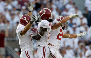 Safeties Vinnie Sunseri and Will Lowery sandwich cornerback Dre Kirkpatrick in celebration.