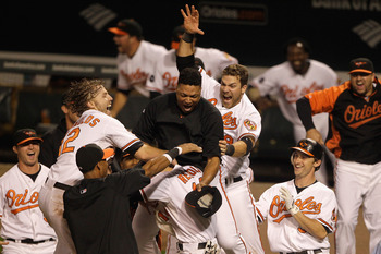 BALTIMORE, MD - SEPTEMBER 28: Members of the Baltimore Orioles swarm Nolan Reimold #14 after he scored the winning run to defeat the Boston Red Sox 4-3 at Oriole Park at Camden Yards on September 28, 2011 in Baltimore, Maryland.  (Photo by Rob Carr/Getty