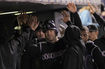 DENVER, CO - SEPTEMBER 17:  Kevin Kouzmanoff #15 of the Colorado Rockies celebrates in the dugout after scoring on a single by Dexter Fowler of the Rockies against the San Francisco Giants in the sixth inning at Coors Field on September 17, 2011 in Denver