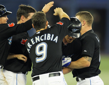TORONTO, CANADA - SEPTEMBER 19:  Adam Lind #26 of the Toronto Blue Jays is mobbed by his teammates after his game winning hit in the bottom of the 10th inning against the Los Angeles Angels of Anaheim in a MLB game on September 19, 2011 at the Rogers Cent