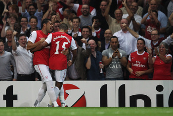 LONDON, ENGLAND - SEPTEMBER 28:  Alex Oxlade-Chamberlain of Arsenal (15) celebrates in front of the Arsenal fans with Andre Santos as he scores their first goal during the UEFA Champions League Group F match between Arsenal and Olympiacos at the Emirates