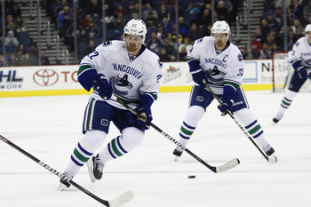 Daniel Sedin (foreground) and Henrik Sedin (background)