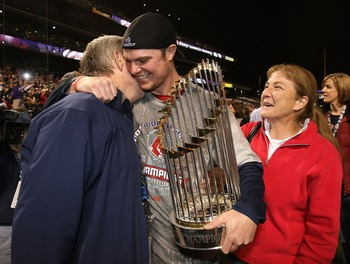 Jon Lester only a year removed from treatment for cancer hugs both his parents and the World Series trophy following game four of the 2007 World Series.