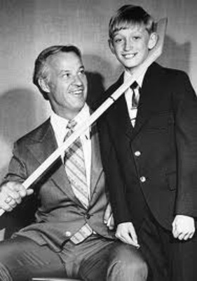 Young Wayne Gretzky having picture taken with Gordie Howe