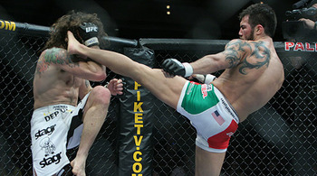 Clay Guida (left) eating a Roger Huerta head kick/ photo cred: Scott Petersen for MMAWeekly.com