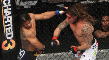 Benson Henderson (left) eating a right from Clay Guida/ photo cred: Laron Zaugg for MMAWeekly.com