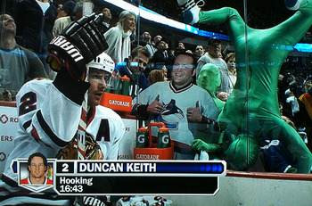 Duncan_keith_in_the_penalty_box_with_the_green_men_and_vince_vaughn__just_another_game_7_in_the_nhl_playoffs_original_display_image
