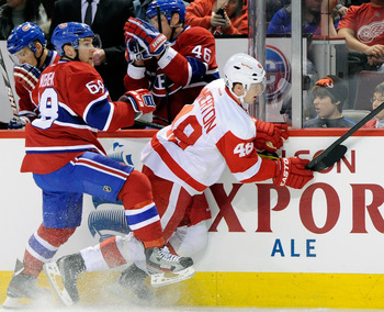 MONTREAL, CANADA - JANUARY 25:  Yannick Weber #68 of the Montreal Canadiens body checks Cory Emmerton #48 of the Detroit Red Wings during the NHL game at the Bell Centre on January 25, 2012 in Montreal, Quebec, Canada.  (Photo by Richard Wolowicz/Getty Im