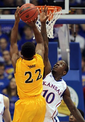 LAWRENCE, KS - DECEMBER 06:  Tyshawn Taylor #10 of the Kansas Jayhawks blocks a shot by Casper Ware #22 of the Long Beach State 49ers during the game on December 6, 2011 at Allen Fieldhouse in Lawrence, Kansas.  (Photo by Jamie Squire/Getty Images)