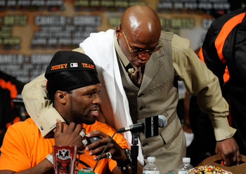 LAS VEGAS, NV - SEPTEMBER 17:  Rapper 50 Cent sits at the table as he is hugged by Floyd Mayweather Jr. during the post-fight news conference after Mayweather Jr. knocks out Victor Ortiz in the WBC welterweight title fight at the MGM Grand Garden Arena on