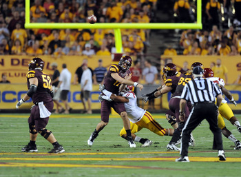 TEMPE, AZ - SEPTEMBER 24:  Brock Osweiler #17 of the Arizona State Sun Devils gets rid of the ball as he gets hit by Nick Perry #8 of the University of Southern California Trojans at Sun Devil Stadium on September 24, 2011 in Tempe, Arizona.  (Photo by No