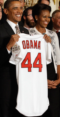 Barack and Michelle Obama hold up the St Louis Cardinals jersey at the team's White House visit.