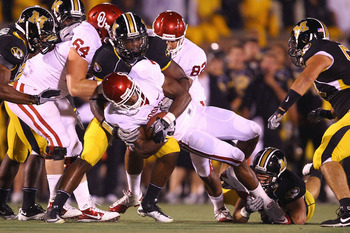Smith (middle), takes down DeMarco Murray in a 2010 Missouri-OU game.