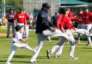 FORT MYERS, FL - FEBRUARY 19:  Designated hitter David Ortiz #34 of the Boston Red Sox warms up with his son Deangelo during a Spring Training Workout Session at the Red Sox Player Development Complex on February 19, 2011 in Fort Myers, Florida.  (Photo b