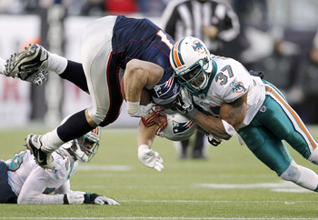FOXBORO, MA - DECEMBER 24:  Rob Gronkowski #87 of the New England Patriots is hit by Yeremiah Bell #37 of the Miami Dolphins during the second half of New England's 27-24 win at Gillette Stadium on December 24, 2011 in Foxboro, Massachusetts.  (Photo by W