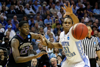 CHARLOTTE, NC - MARCH 20:  Justin Holiday #22 of the Washington Huskies and John Henson #31 of the North Carolina Tar Heels go after a loose ball in the first half during the third round of the 2011 NCAA men's basketball tournament at Time Warner Cable Ar